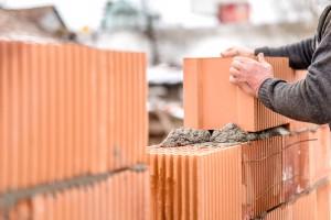 construction mason worker bricklayer installing brick walls