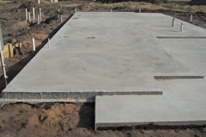 Concrete slab prepared for residential house construction with utility pipes within slab