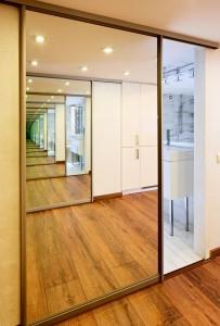 Sliding-door mirror wardrobe in modern hall interior with infinityreflections