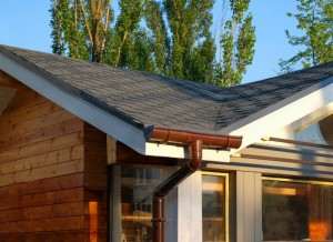 Rain gutter system with bitumen roof shingles on a wooden house.